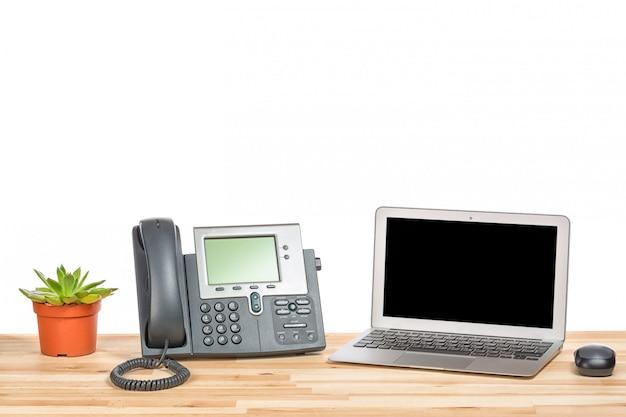 モダンなip電話、ポットの植物、軽い木製のテーブルの上のコンピューターのマウスとラップトップコンピューター。