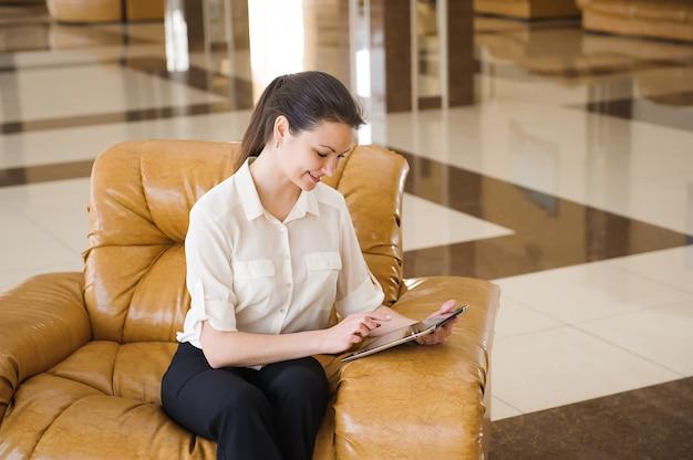 Ipadに取り組んで忙しいビジネスの女性の肖像画