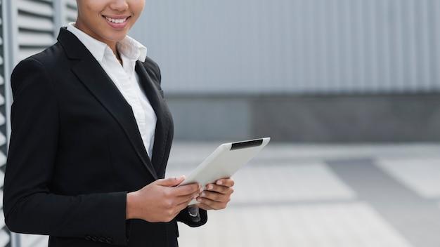 Ipadを保持している成功した女性をクローズアップ