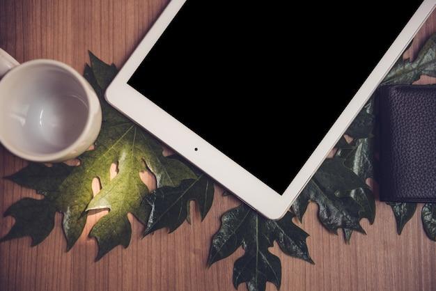 Ipad、コーヒーマグ、グラス、財布がある机の上。