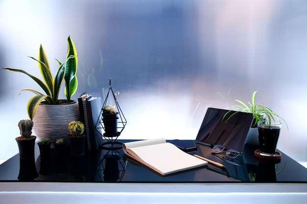 ガラステーブルの上の現代のipadと職場、黒い画面、観葉植物と消耗品を模擬。