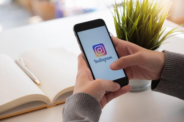 Женщина держит iphone 6s с приложением instagram на экране в кафе. instagram - это приложение для обмена фотографиями для смартфонов