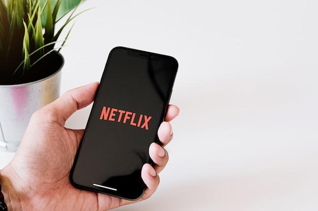 Iphone xsでnetflixロゴを持つスマートフォンを持つ女性の手。 netflixは、ストリーミング映画とテレビシリーズのグローバルプロバイダーです。