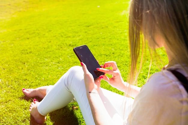彼女の柔らかい腕の中で、iphoneの背中から女性の肩を見る