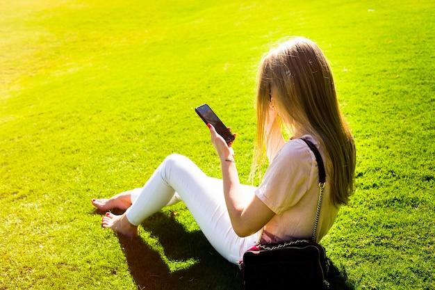 エレガントな女性は、公園の緑の芝生に座って自分のiphoneをチェックします