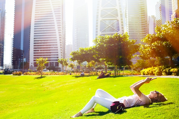 明るい夏の太陽が緑の芝生に横たわっている女性の上に光り、公園で彼女のiphoneをチェックする