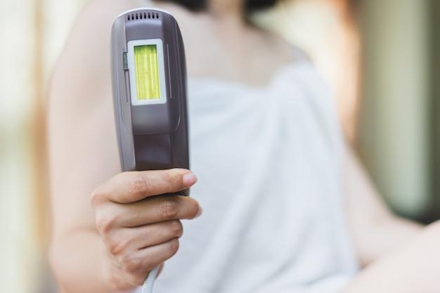 自宅でスキンケアのために準備するiplレーザー脱毛を持つ女性