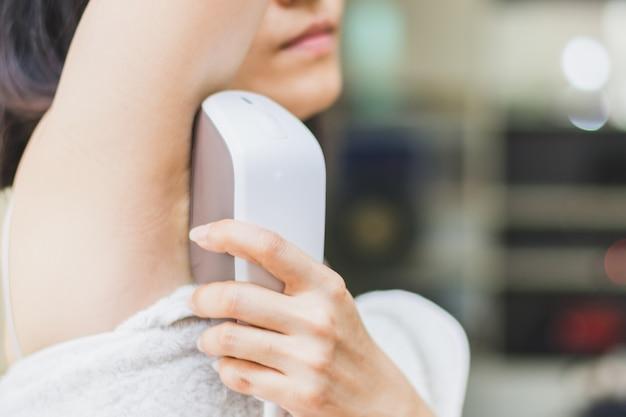 女性が個人的なiplレーザー脱毛を使用して自宅でスキンケアの準備