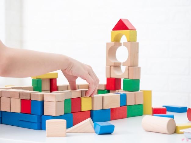 白いテーブルに木製のブロックを再生しながら子供の手を閉じます。ブロックをすることは、子供のiq、eq、スキルと脳を発達させています。