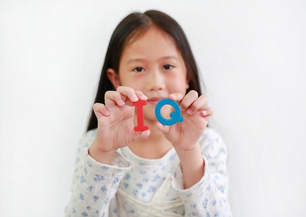 흰색 배경 위에 여자 아이 손에 iq(지능 지수) 스폰지 텍스트. 아이와 교육 개발 개념