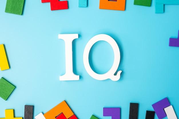 다채로운 나무 퍼즐 조각이 있는 iq 텍스트, 파란색 배경에 기하학적 모양 블록. 지능 지수와 논리 사고의 개념