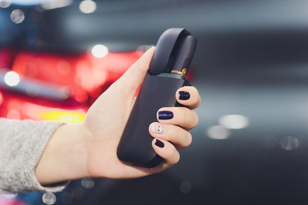 Технология табачных изделий, не перегреваемых iqos. женщина, держащая электронную сигарету в руке перед курением.