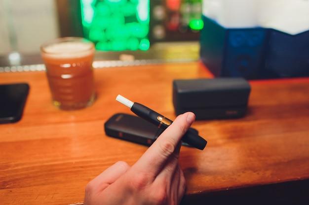 Iqos熱焼けタバコ製品テクノロジー。喫煙する前に彼の手で電子タバコを保持している男。