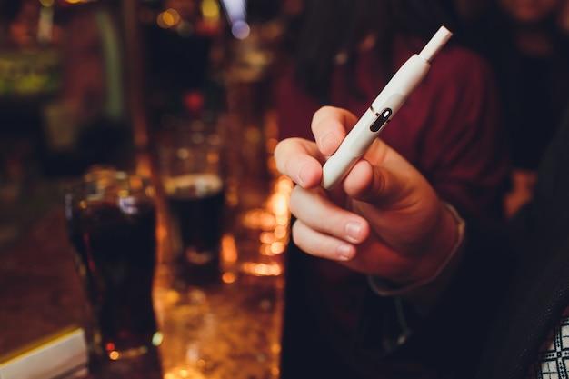 Iqosの非燃焼たばこ製品テクノロジー。喫煙する前に彼の手で電子タバコを保持している男。