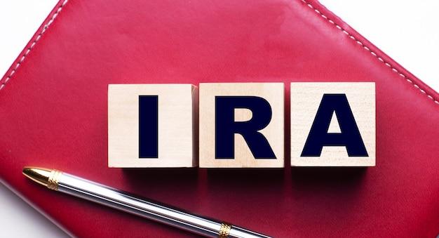 Индивидуальный пенсионный счет ира состоит из деревянных кубиков, которые стоят на бордовом блокноте рядом с ручкой. бизнес-концепция