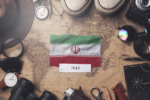 Iran flag between traveler's accessories on old vintage map. overhead shot