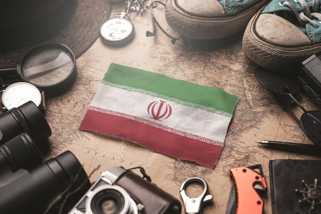 Iran flag between traveler's accessories on old vintage map. tourist destination concept.