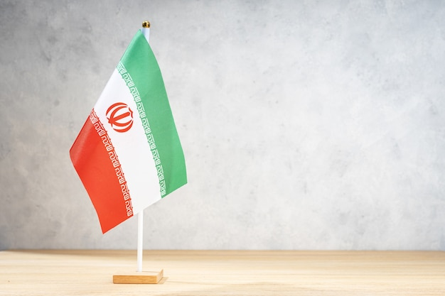 Iran table flag on white textured wall. copy space for text, designs or drawings