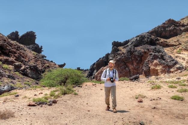 이란의 hormuz 섬, 배낭과 카메라가있는 성숙한 남자 관광객은 산길을 따라갑니다.
