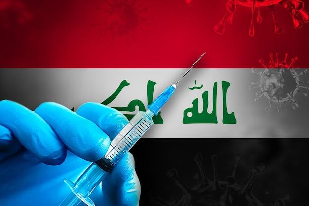 이라크 코비드19 예방 접종 캠페인 파란색 고무 장갑을 끼고 깃발 앞에 주사기를 들고 있습니다