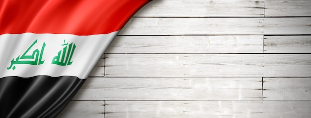 Iraq flag on old white wall. horizontal panoramic banner.