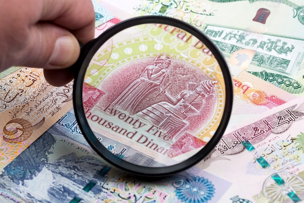 Iraqi dinar in a magnifying glass