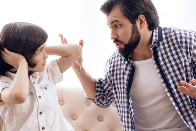 Irate father scolds teenage son which plugs ears.