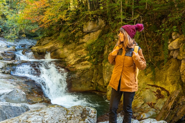 Irati forest or jungle in autumn, a young hiker in the cubos waterfall. ochagavia, northern navarra in spain