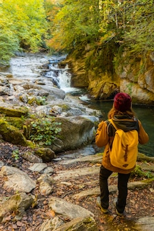 Irati forest or jungle in autumn, a young woman at the cubos waterfall. ochagavia, northern navarra in spain