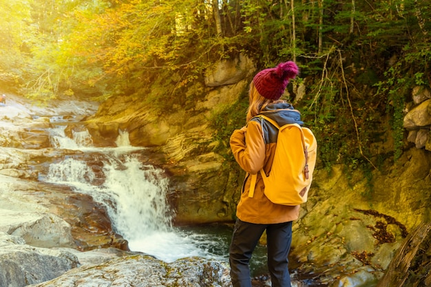 Irati forest or jungle in autumn, a young woman at sunset in the cubos waterfall. ochagavia, northern navarra in spain