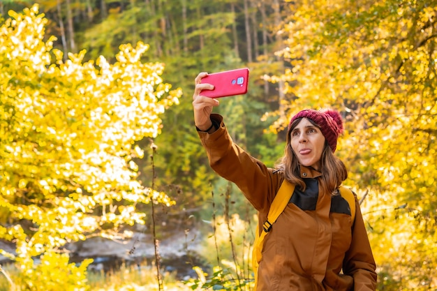 Irati jungle or in autumn, lifestyle, a young hiker taking a selfie sticking out her tongue in the forest. ochagavia, northern navarra in spain, selva de irati