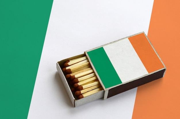 Ireland flag  is shown in an open matchbox, which is filled with matches and lies on a large flag