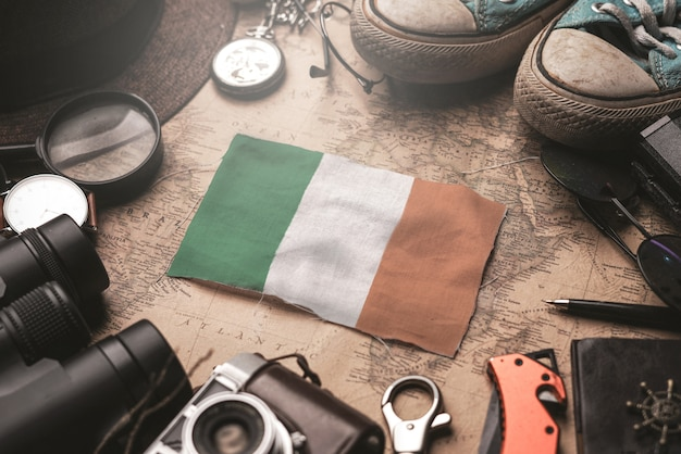 Ireland flag between traveler's accessories on old vintage map. tourist destination concept.
