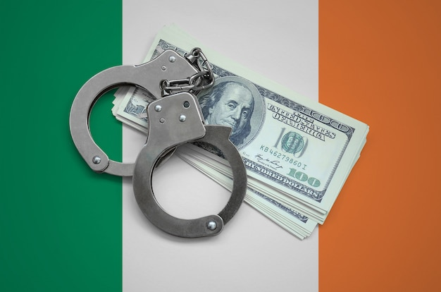 Ireland flag  with handcuffs and a bundle of dollars. currency corruption in the country. financial crimes