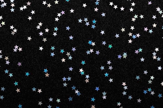 Iridescent silver stars confetti on black festive background glowing sparkles.