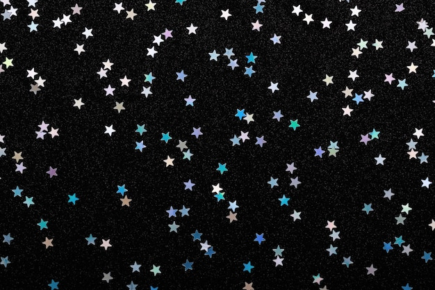 黒のお祭りの背景に虹色の銀の星紙吹雪輝く輝き。