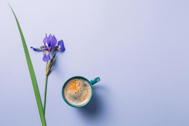 紫色の表面上のコーヒーのカップとアイリスblueflagの花