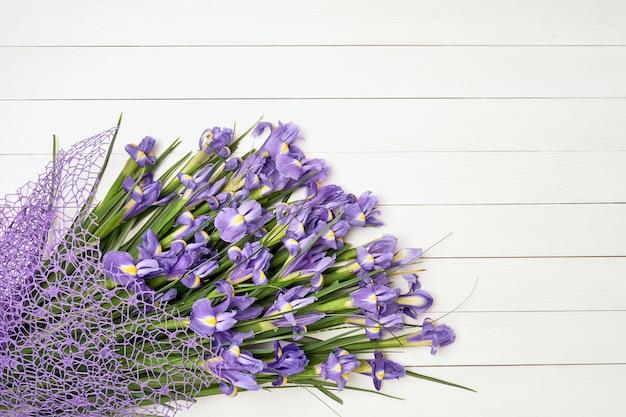 Iris bouquet on white wooden background.