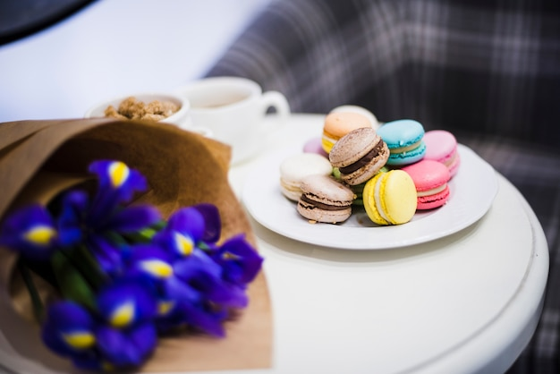 Iris bouquet with colorful macaroons on white plate