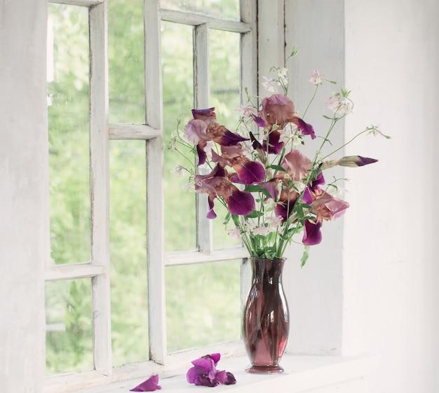 Цветы ириса в стеклянной вазе на белом старом подоконнике