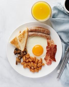 Ирландский классический завтрак яичница жареные сосиски грибы бекон фасоль кофе апельсиновый сок