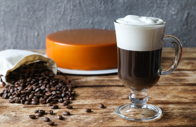 Irish coffee with cake in the  and coffee beans in a bag
