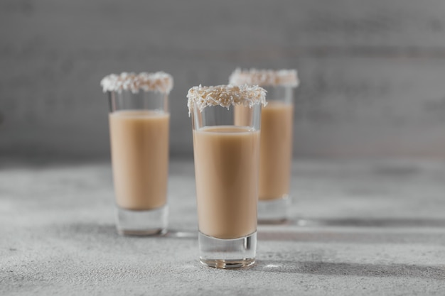 짧은 글래스 위에 코코넛 플레이크 왕관을 얹은 아일랜드 크림 주류 또는 커피 리큐어. 겨울 휴가 장식