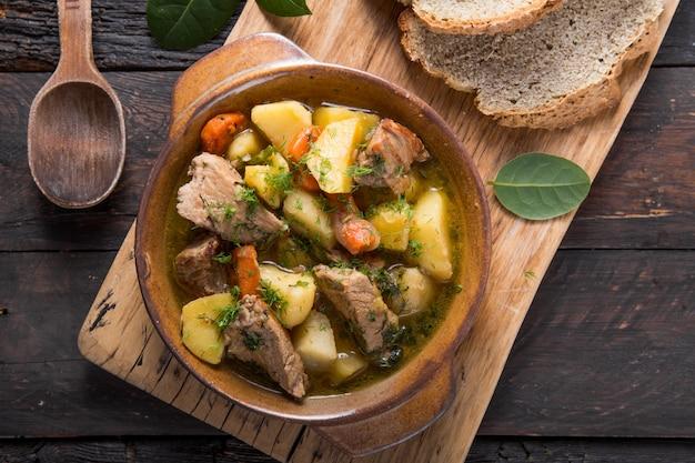 Ирландский ужин мясо говядины тушеное с картофелем, морковью и содовым хлебом на деревянном столе, вид сверху, копией пространства. домашняя зимняя уютная еда - медленно готовится