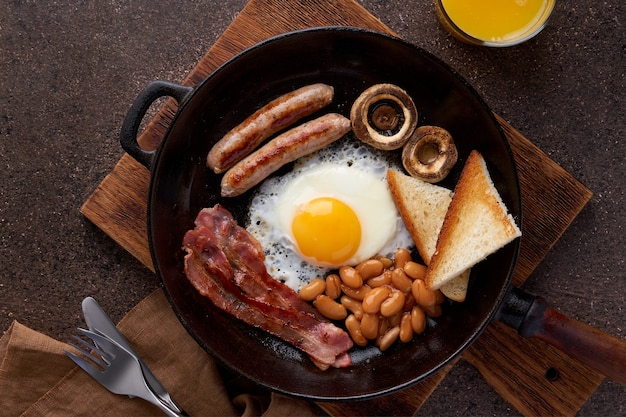 Irish fat morning breakfast with eggs bacon mushrooms sausages toast beans and orange juice