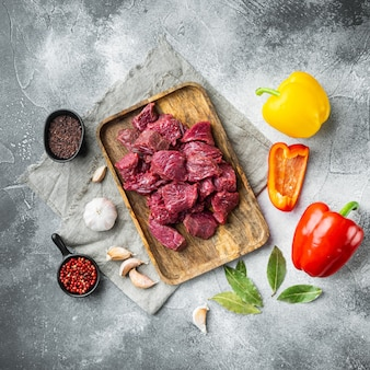 Irish raw beef stew recipe ingredients set with sweet bell pepper, on gray stone background, top view flat lay, square format