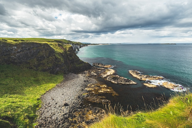 Irish shoreline under the cloudy sky background. northern ireland. green covered land surrounded by the water surface. picturesque irish landscape. perfect place for the outdoor activity.