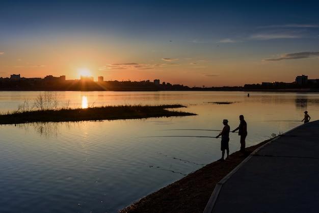 Иркутск, россия - 13 июня 2020 года: силуэт мужчины и ребенка, рыбалка на набережной реки ангара в лучах заходящего солнца