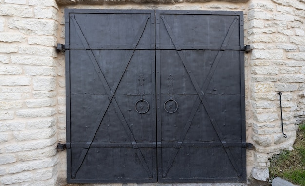 An iron black heavy locked door of a stone building an ancient castle