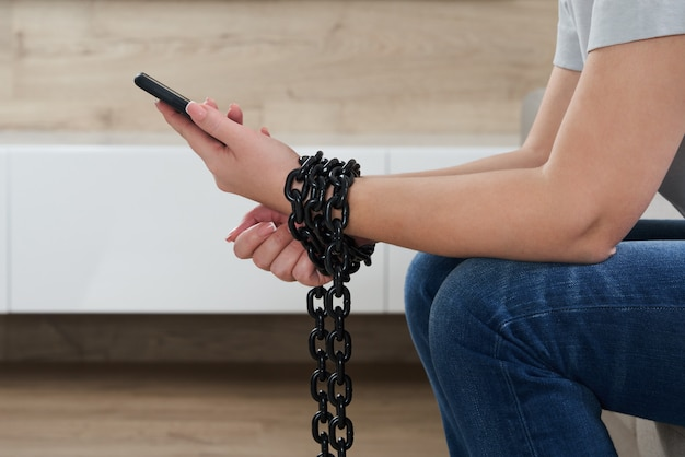 Железная цепь, соединяющая руку и смартфон